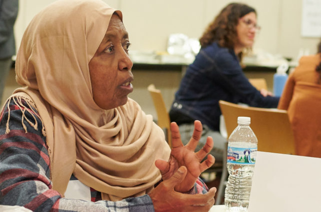 Woman in 60's in hijab talking at table of people