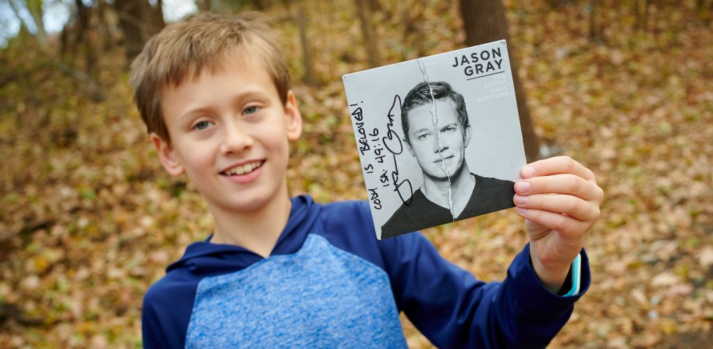 9 year old boy outside holding Jason Gray music CD