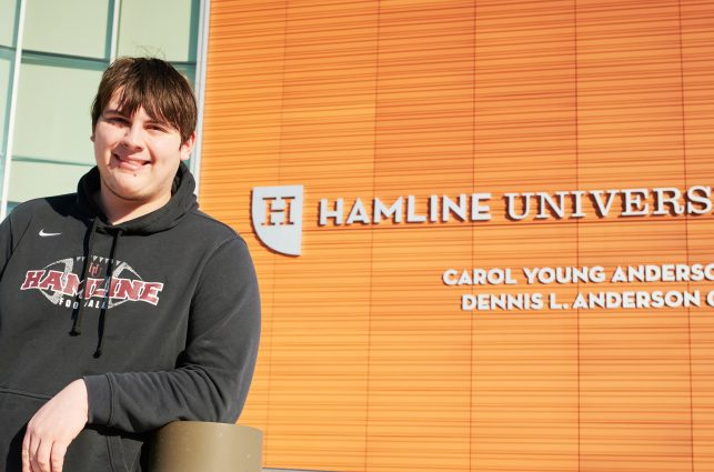 White male college student smiling in front of Hamline University sign