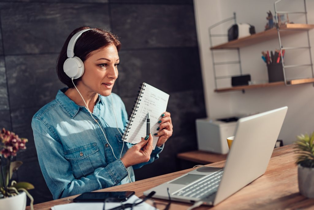 Women sitting in front of computer with headphones on