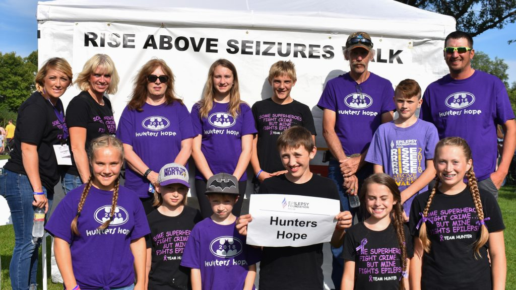 Group of 14 people of all ages smiling at Rise Above Seizures Walk