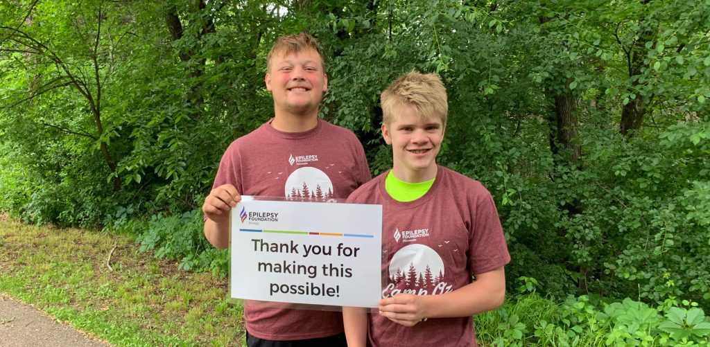 Two boys holding a sign that says Thank You