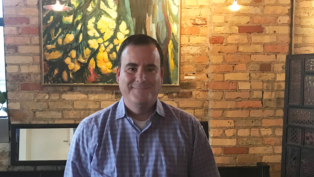 Middle-aged man looks directly at the camera in front of a brick cafe wall.