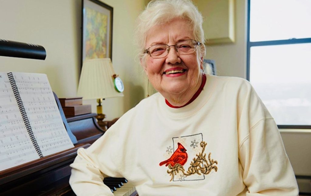 Older woman in a cardinal sweater with a big smile sits in front of a piano.