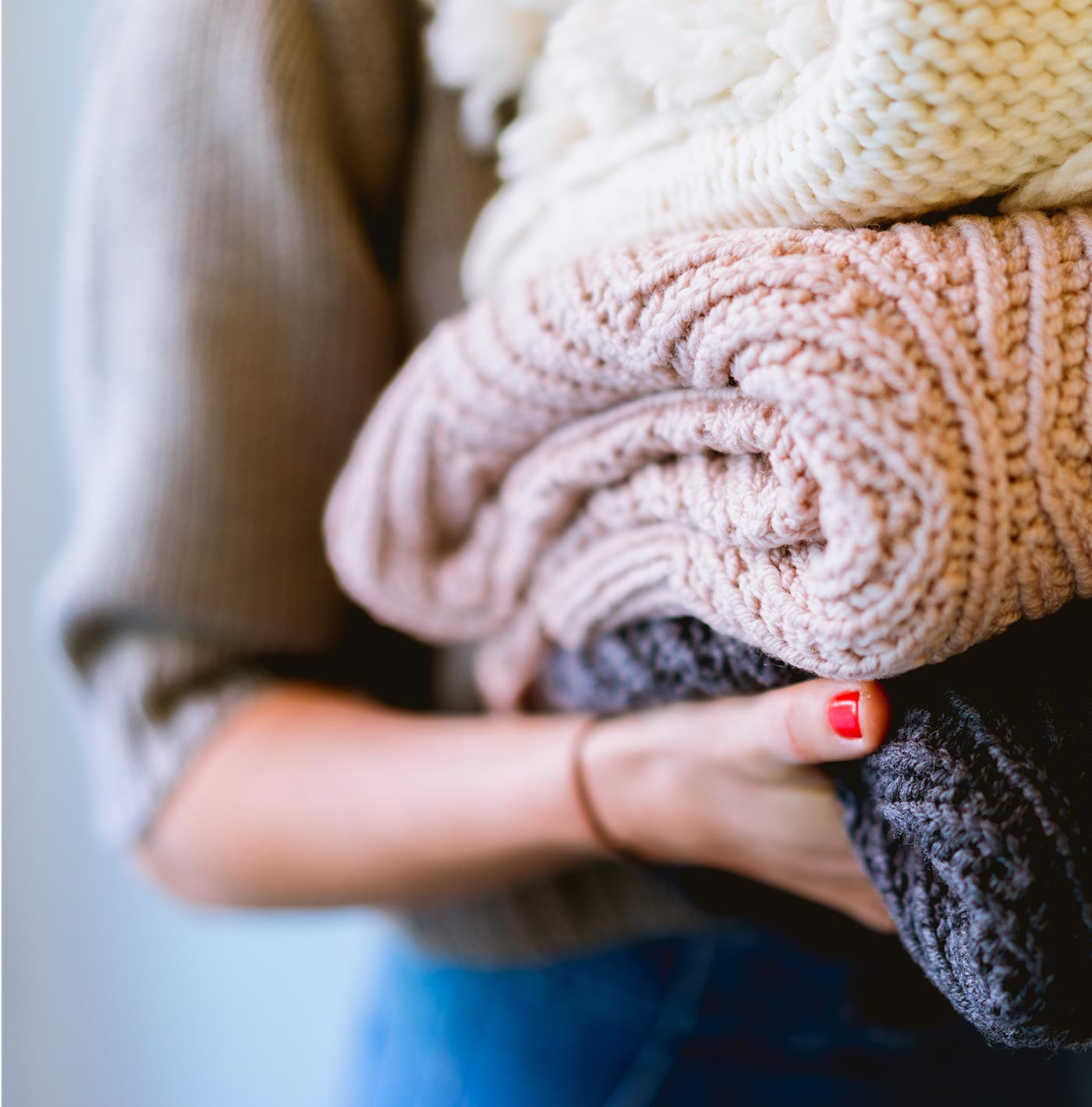 Close-up of a person holding a stack of folded knit sweaters.